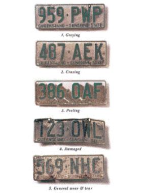 A selection of number plates showing different types of wear and tear including greying of colour, crazing and peeling of the surface, damage and general wear and tear to the number plate.