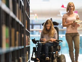 Woman in wheelchair looking at library books