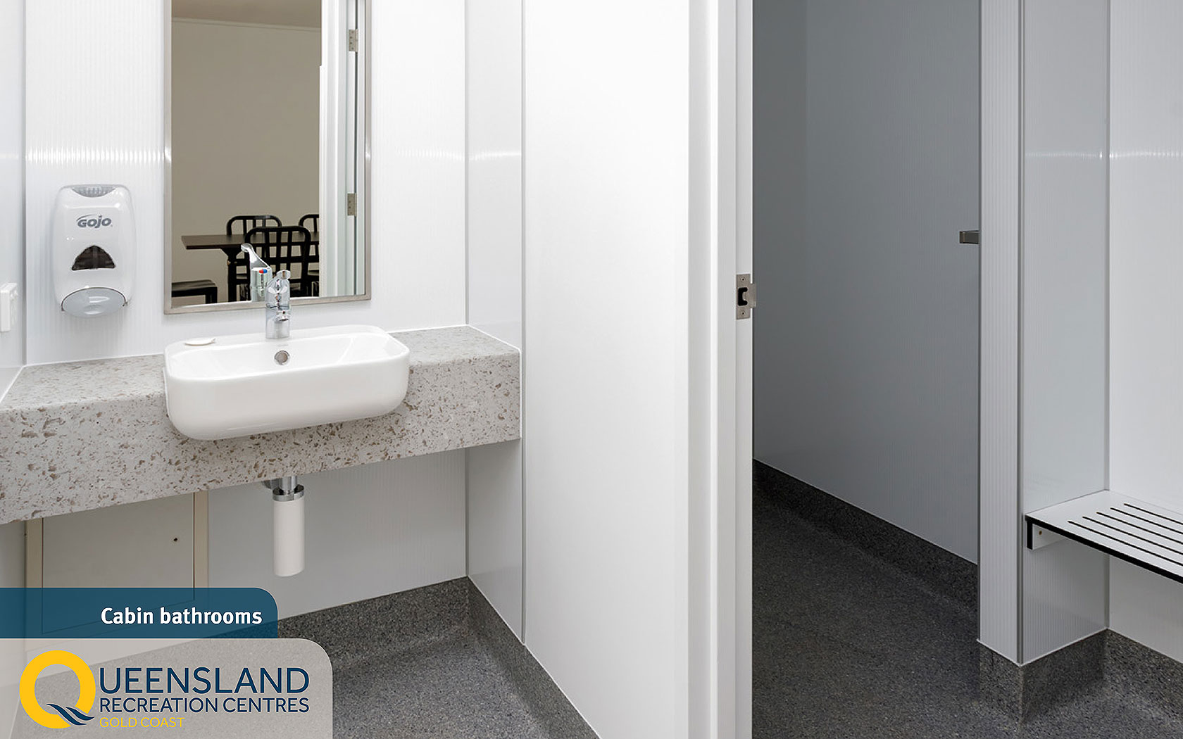 Standard cabin adjoining bathroom with separate shower, mirror, sink and accessible dispensers at the Gold Coast Recreation Centre