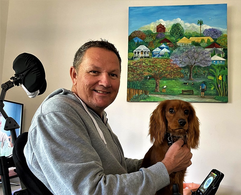 Clem sits in his wheelchair with pet dog and his painting on the wall