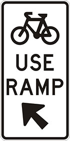 white sign with black icon of a bicycle, the words use ramp, and an arrow