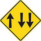 yellow diamond-shaped sign with 1 arrow pointing upward and 2 parallel arrows pointing downward