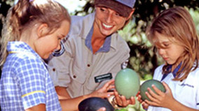 Two students holding cassowary eggs with a park ranger.