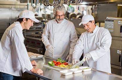Teacher teaching students cooking techniques
