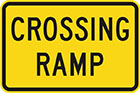 yellow sign with black text, crossing ramp