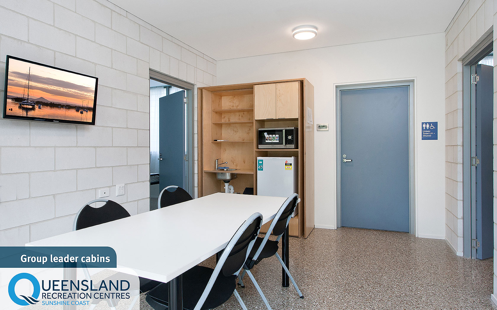 Group leader cabin interior with table, chairs, kitchenette and adjoining bedrooms at the Sunshine Coast Recreation Centre