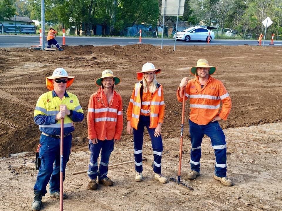 Four people in high visibility clothing standing on work site