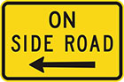 yellow sign with black arrow to left (or right) and text, on side road