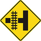 yellow diamond-shaped sign with black T shape with rail tracks, showing how they intersect the road