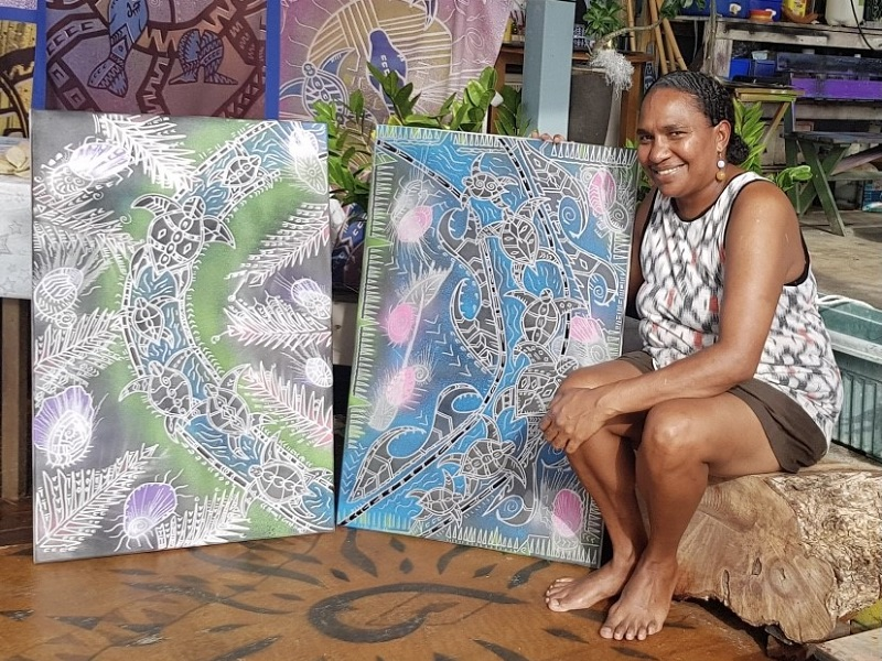 Moana sits barefooted with a selection of her artworks