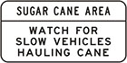 white sign with black text, sugar cane area. Watch for slow vehicles hauling cane