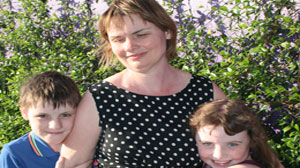 Karen Knight is hugged by her school age son and daughter.