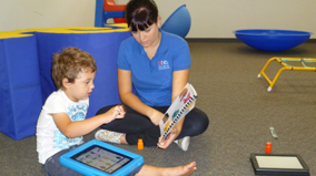 A speech pathologist from the AEIOU Foundation uses an iPad with a young boy who participates in an early intervention program.