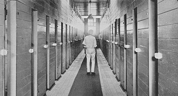 Man stands in a narrow brick corridor with doors along both sides.