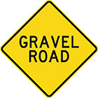 yellow diamond-shaped sign with black text, gravel road