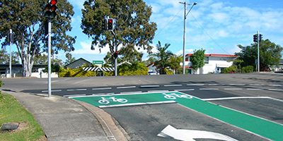 bicycle storage area, an intersection with green painted areas and white bicycle symbols