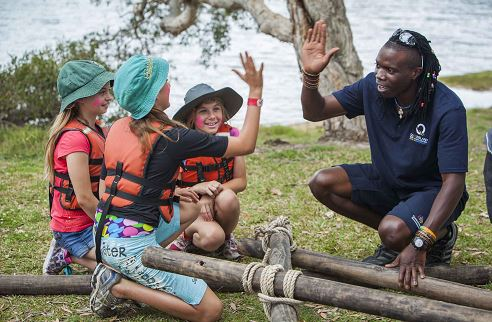 Children learning how to build a raft.