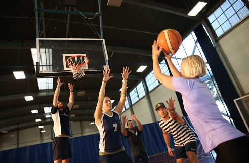 People playing basketball on an indoor court.