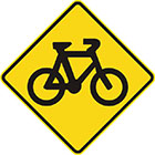 yellow diamond-shaped sign with black image of a bicycle