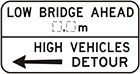white sign with black arrow and text, low bridge ahead, number of metres. High vehicles detour