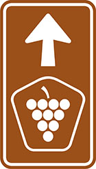 brown sign with arrow and pentagonal badge with grapes icon