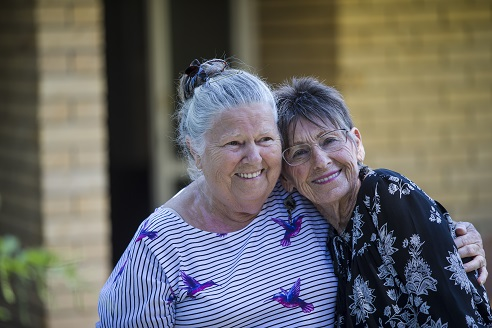 Two elderly friends smiling and embracing