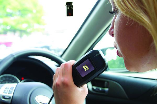 Woman breathing into interlock device in vehicle