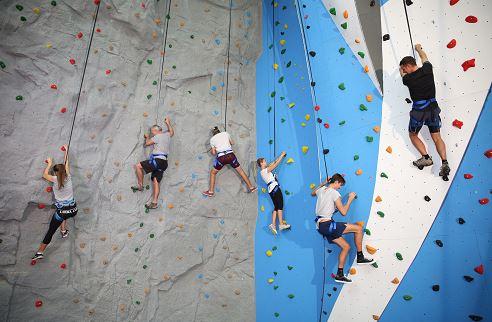 People climbing an indoor climbing wall.